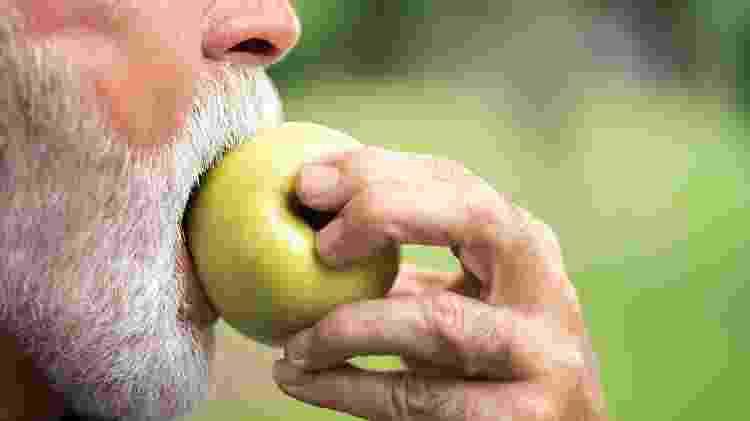 homem comendo maçã; fruta - iStock - iStock