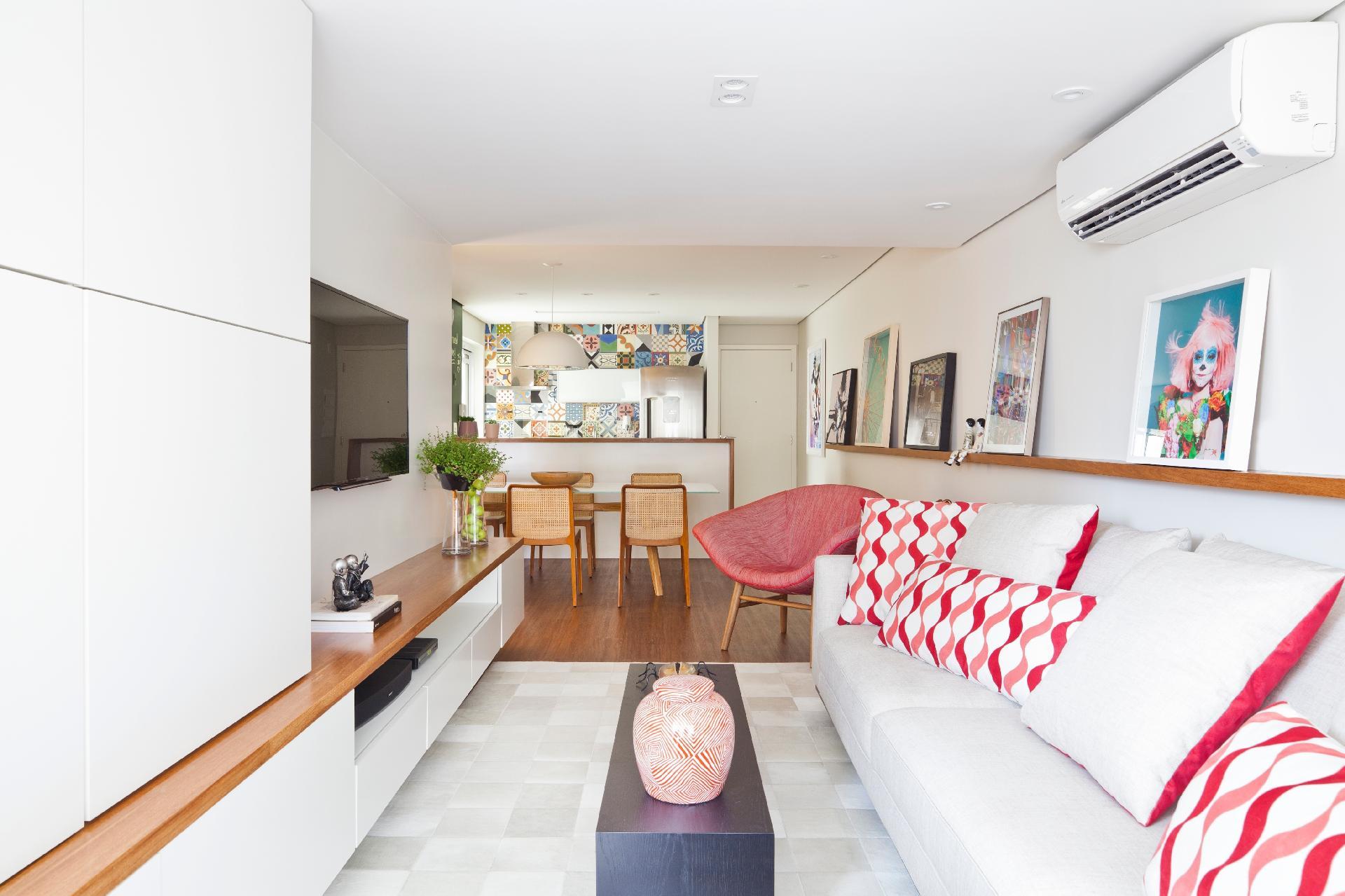 O apê da moça tem um visual leve e feminino, com marcenaria em laca branca e madeira clara e pinceladas de cor nos objetos, como almofadas e quadros. A sala foi ampliada com a integração da varanda 'gourmet', no projeto de reforma executado pelos arquitetos do escritório Conrado Ceravolo, em São Paulo