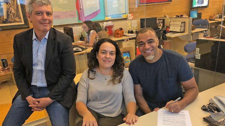 Denilson assina renovação de contrato com a Band ao lado de Humberto Candil, diretor executivo de esportes, e Denise Santana, diretora de recursos artísticos - Divulgação/Band