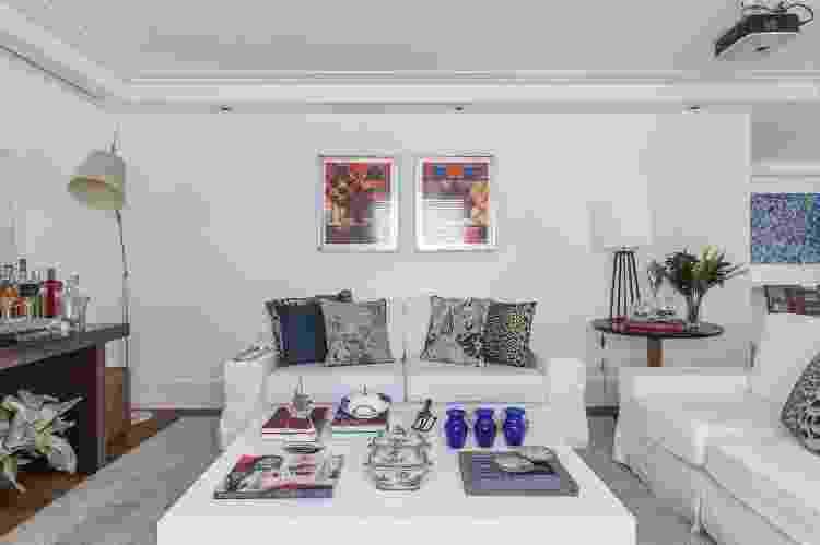Neste projeto, a arquiteta optou por sofás mais despojados, com capas de sarja branca. Assim, deixou para inserir as cores no restante do ambiente como nas almofadas, objetos e quadros, assim como no tapete com textura - Rafael Renzo - Rafael Renzo