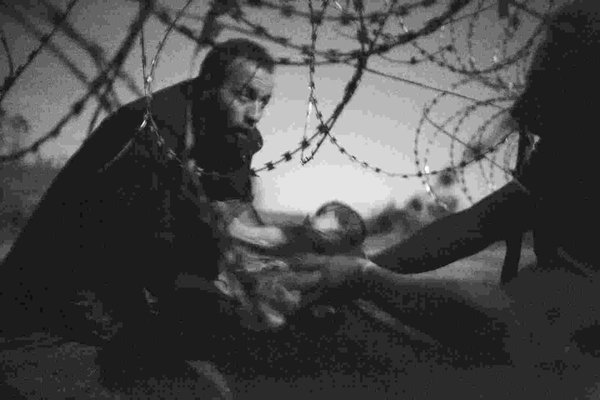 18.fev.2016 - A fotografia que ganhou o prêmio World Press Photo (WPP), do australiano Warren Richardson. A imagem em branco e preto mostra um homem passando um bebê através de uma cerca de arame na fronteira entre a Sérvia e a Hungria. - Warren Richardson/World Press/EFE