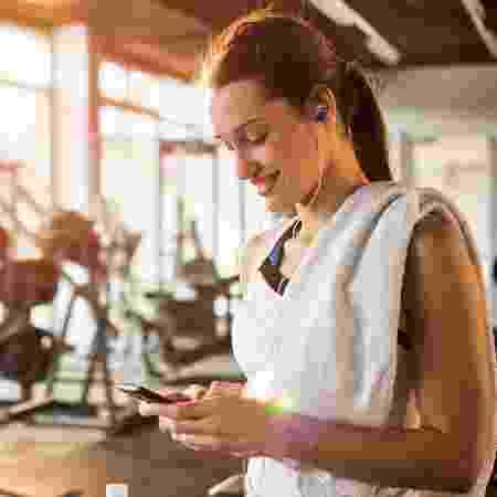 Mulher na academia com celular - iStock - iStock