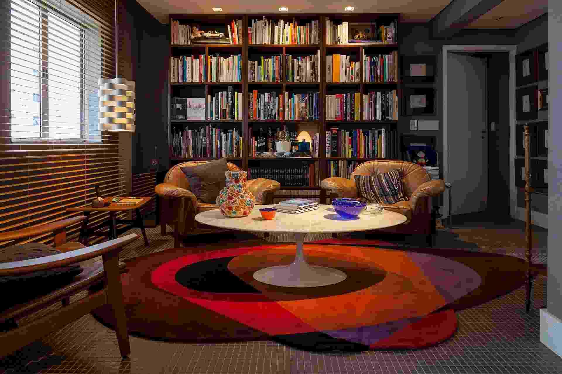 Com cores sóbrias, da pastilha cinza a madeira escura dos móveis, a sala ganhou vida e alegria com o tapete circular colorido (Punto e Filo), que se assemelha a uma obra de arte. Os tons da peça conversam com os demais presentes em objetos. Projeto da Díptico Design de Interiores - Júlia Ribeiro/Divulgação