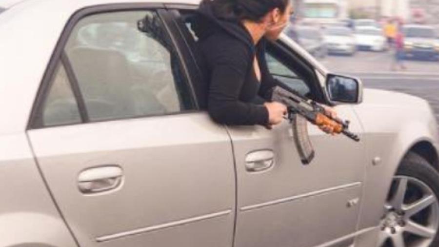Mulher posa com AK47 em Cadillac - Reprodução