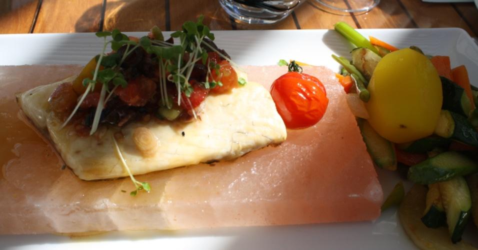 Robalo servido em uma pedra de sal com vegetais, prato do L'Horizon e Champagne Bar