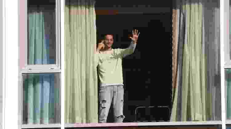 Roger Gonçalves, que é do Brasil e viajou por Madri para chegar ao Reino Unido, acena da janela do Hotel Radisson - PA MEDIA - PA MEDIA