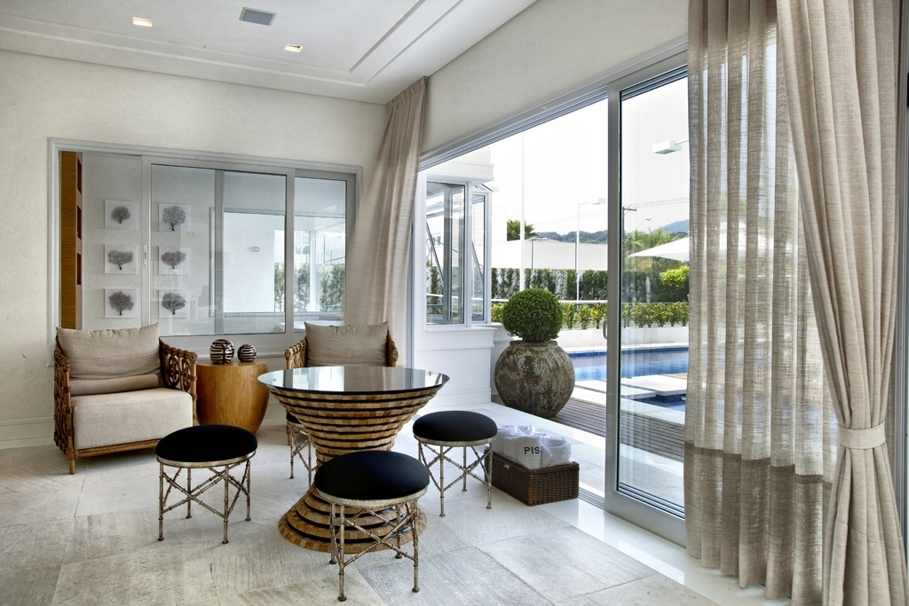 O estar com TV integra piscina, sauna e churrasqueira, além da sala de hidromassagem. O piso é feito de pedra mineira, a  mesma que pavimenta outras áreas molhadas. Nas paredes, o revestimento é o Originale, da TerraCor, um tipo de pintura texturizada. A casa Acapulco tem projeto de interiores assinado por Bianka Mugnatto