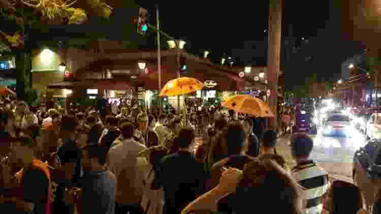 "Seguindo guarda-chuvas de cor laranja, participantes do ""pub crawl"" cruzam a Vila Madalena - Marcel Vincenti/UOL"