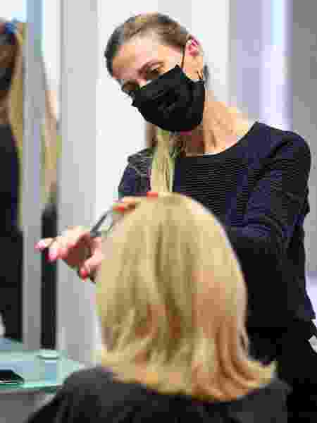 Cabeleireira corta cabelo de uma cliente em um salão de beleza após abertura do comércio na Alemanha - Getty Images
