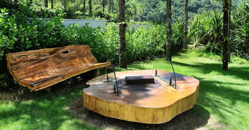 A área externa também pode ser desfrutada no inverno, se equipada com uma lareira. No projeto da designer de interiores Lidia Damy Sita, o jardim da casa de praia foi adaptado aos dias frios com os móveis de madeira da Monica Cintra, que acoplou a lareira na mesa de centro