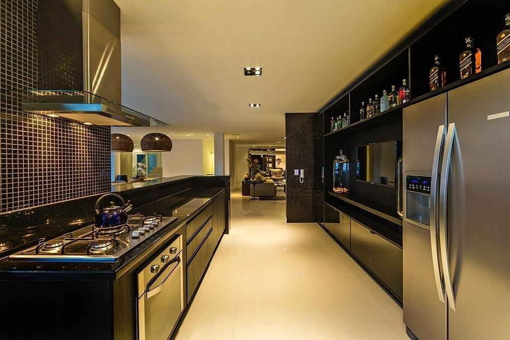 Na ampla cozinha desta casa em Balneário Camboriú (SC), os eletrodomésticos de aço foram combinados aos acabamentos escuros que levam granito São Gabriel na bancada (à esq.), marcenaria em MDF e pastilhas cerâmicas. O projeto de arquitetura é de Carolina e Guto Biazzetto, do escritório EB Arquitetura