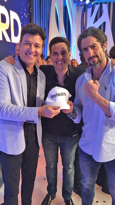 """Faro, Mion e Luiz Bacci seguraram um boné, enviado pela equipe do """"Pânico"""", com a hashtag #SomosTodosBritto - Divulgação"""