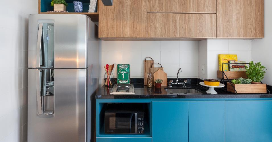3,51 m². Para driblar a metragem reduzida do ambiente, o escritório doob Arquitetura deixou cozinha e sala integrados, usando a bancada de refeições para demarcar os espaços. O azul petróleo, que marca a marcenaria, deu um toque especial ao projeto.
