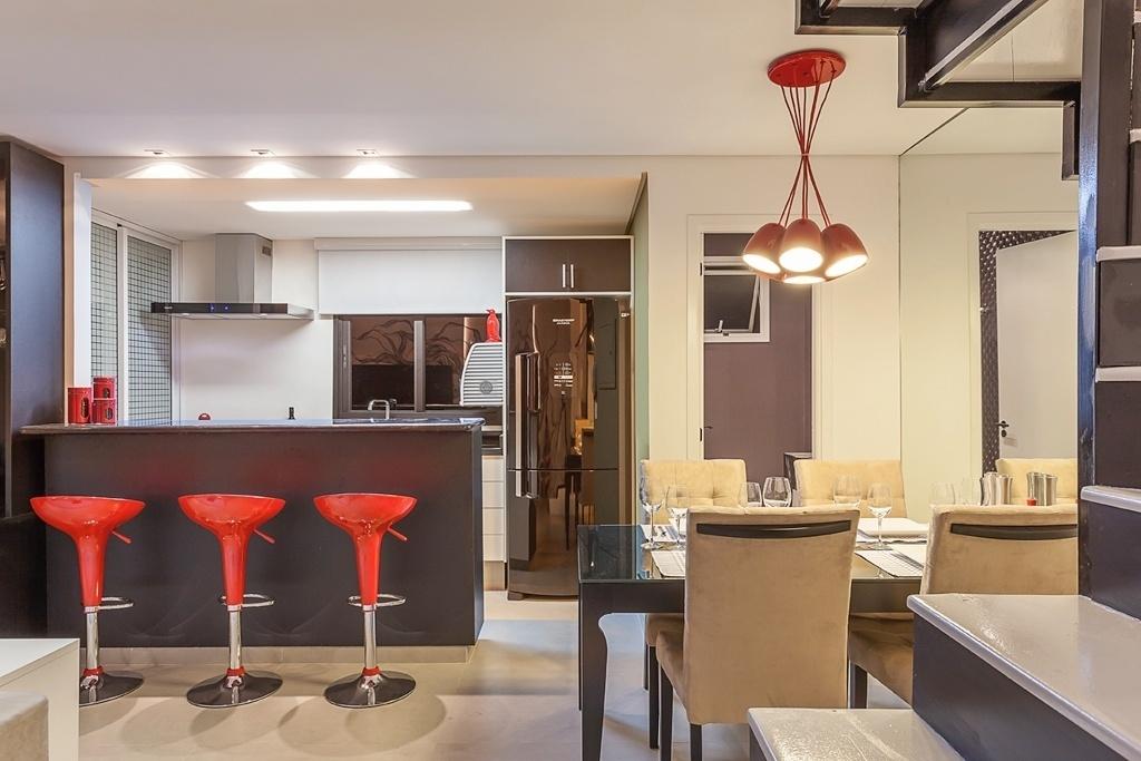Ao integrar a cozinha ao living, André Bove e Felipe Raduan conseguiram dar uma sensação de amplitude para o apartamento. O cômodo com 4,5 m² é equipado com pia, coifa e bancada para refeições rápidas. A paleta de cores neutras, associada ao vermelho, unifica os espaços