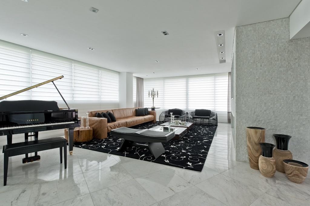 A sala de estar da casa Alphaville tem lareira (à dir.) revestida com mosaico de mármore branco, que difere do tom usado no piso de mármore piguês.