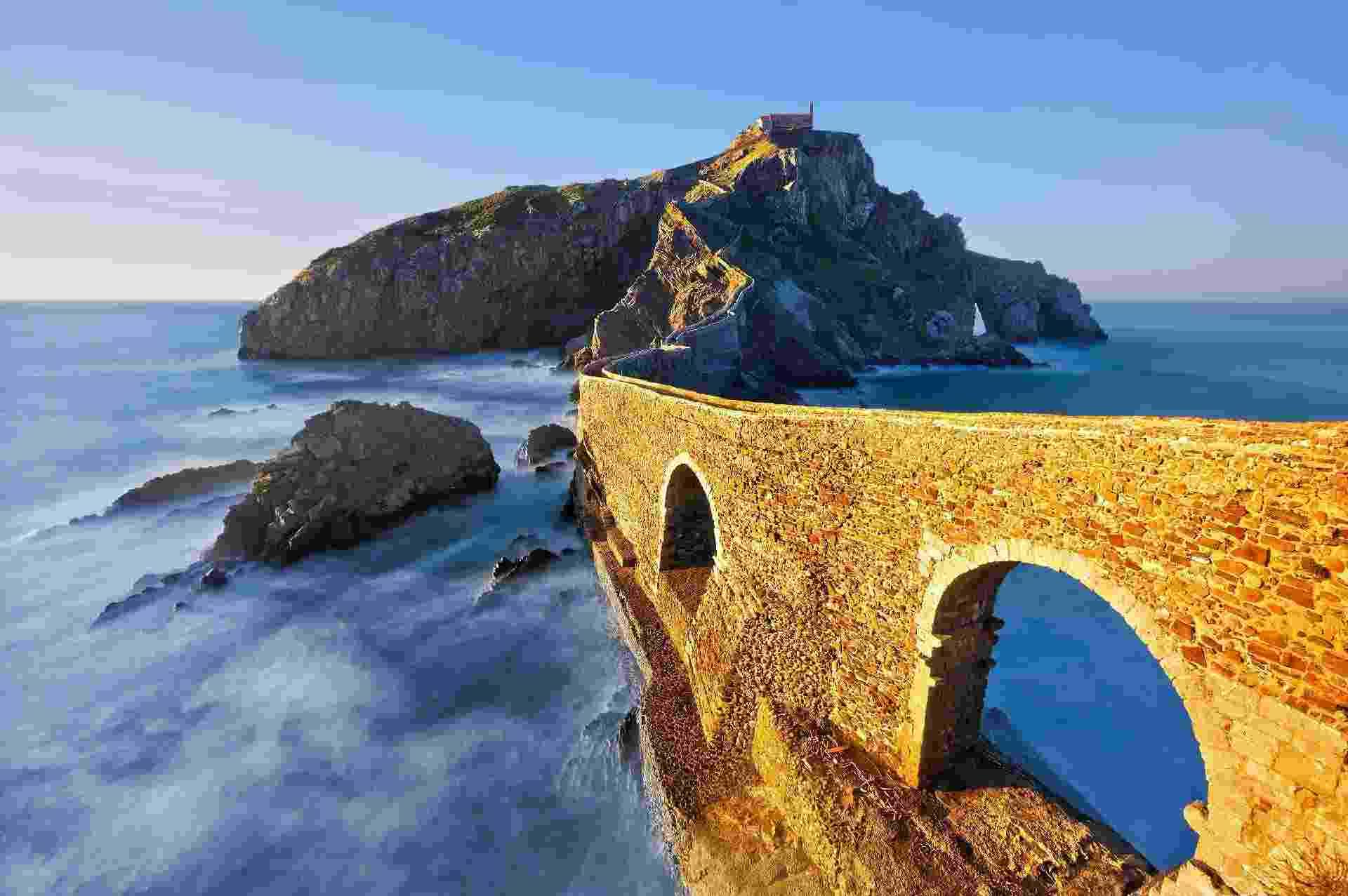 Ligada ao continente por uma ponte de pedra sinuosa e uma escada enorme, o local--em Bermeo, País Basco--se destaca pela imponência. A pequena ilha conta com uma igreja antiga e está rodeada pelo agitado mar do litoral basco. As gravações ocorreram em outubro do ano passado, visto que, segundo o departamento de turismo local, o elenco precisava de um lugar que proporcionasse um ?clima de inverno?. - Getty Images/Divulgação/Skyscanner
