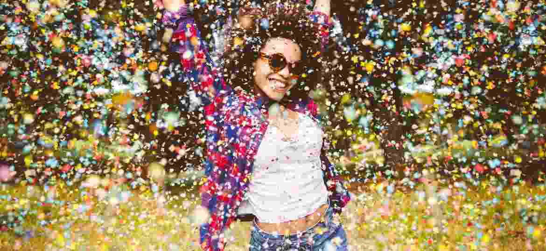 mulher feliz, chuva de confetes - Getty Images