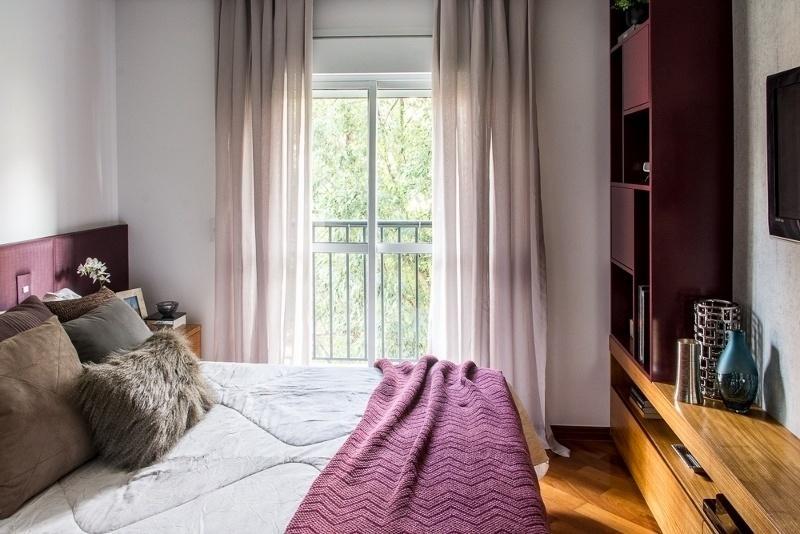 O móvel multifuncional à frente da cama reúne estante, rack e painel para TV, guardando grande parte dos pertences do casal