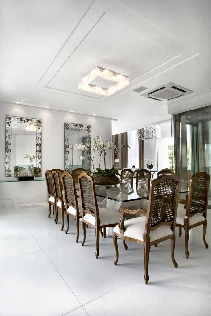 O hall de entrada também se comunica com a sala de jantar. Nela, a mesa usa como base uma escultura de Eliete Vilela e seu tampo de vidro oferece espaço para 12 lugares. As cadeiras escolhidas combinam madeira e palha e os aparadores são de vidro. À direita, uma caixa de aço inox e vidro abriga o elevador panorâmico da casa Acapulco, com interiores assinados por Bianka Mugnatto