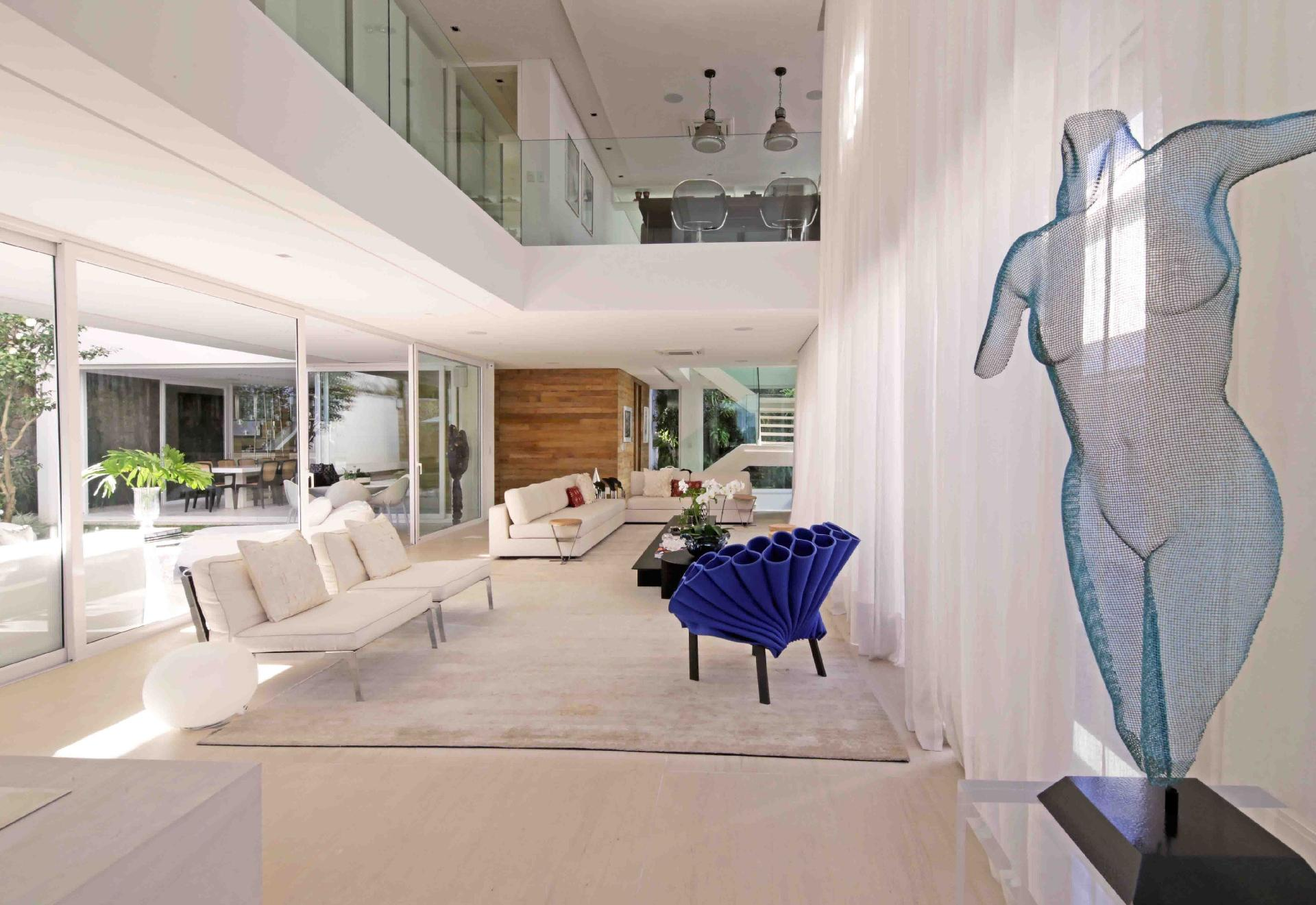 Nas casas do condomínio Bauhaus, projetado pela arquiteta Monica Drucker, os ambientes se integram horizontal e verticalmente, como em um loft. O pé-direito com 5,6 m no estar permite a visualização de diversos espaços da casa. A decoração contemporânea tem detalhes azuis, como a escultura e a poltrona (Brentwood)