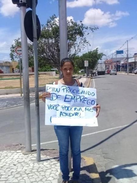 Maryane segura o cartaz usado para pedir emprego em um sinal na cidade de Juazeiro (BA) - Arquivo pessoal
