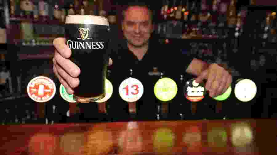 Dono do pub Paddy Cullen, em Dublin (Irlanda), mostra um chope da tradicional Guinness - Getty Images