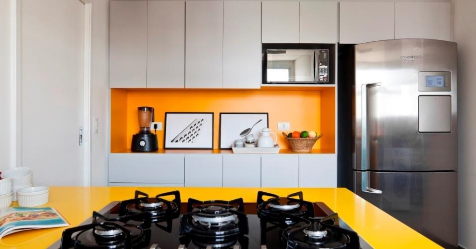 A cozinha era pequena, por isso um quarto de empregada foi demolido e o espaço incorporado para acomodar o armário revestido com laminado melamínico cinza e amarelo e a geladeira (Brastemp Inverse). Na ilha de cocção, o 'cooktop' (Electrolux) fica apoiado sobre bancada (Vulcana Stone - Yellow Regolare) amarela. O projeto é do escritório Iná Arquitetura
