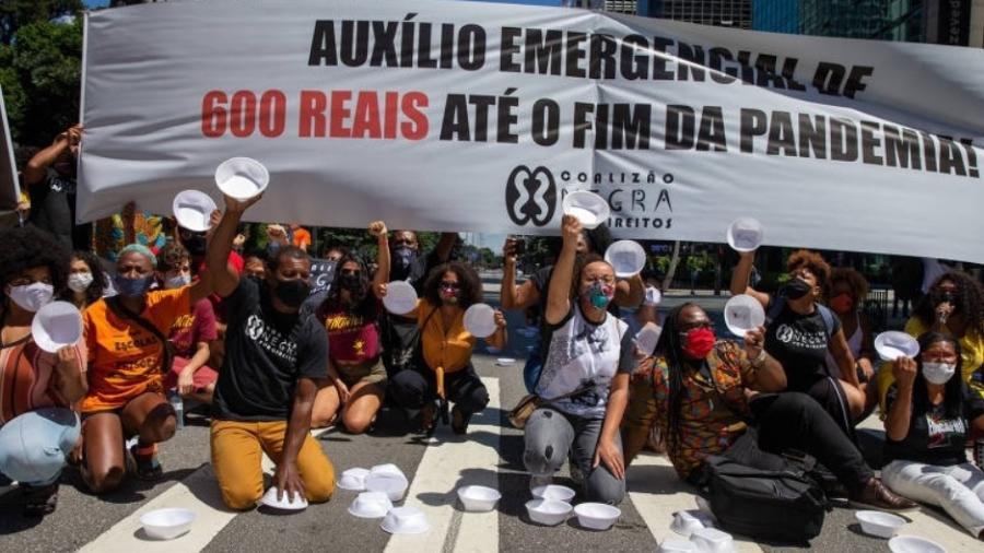 Manifestantes levantam marmitas vazias em protesto na av. Paulista, em SP, em março, pedindo a manutenção do auxílio emergencial - Danilo Verpa/Folhapress