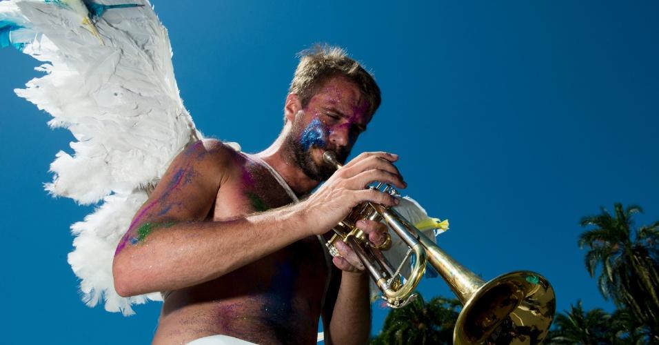 9.fev.2016 - Anjo do bloco Orquestra Voadora toca o trompete para anunciar que o Carnaval continua nesta terça-feira (9)