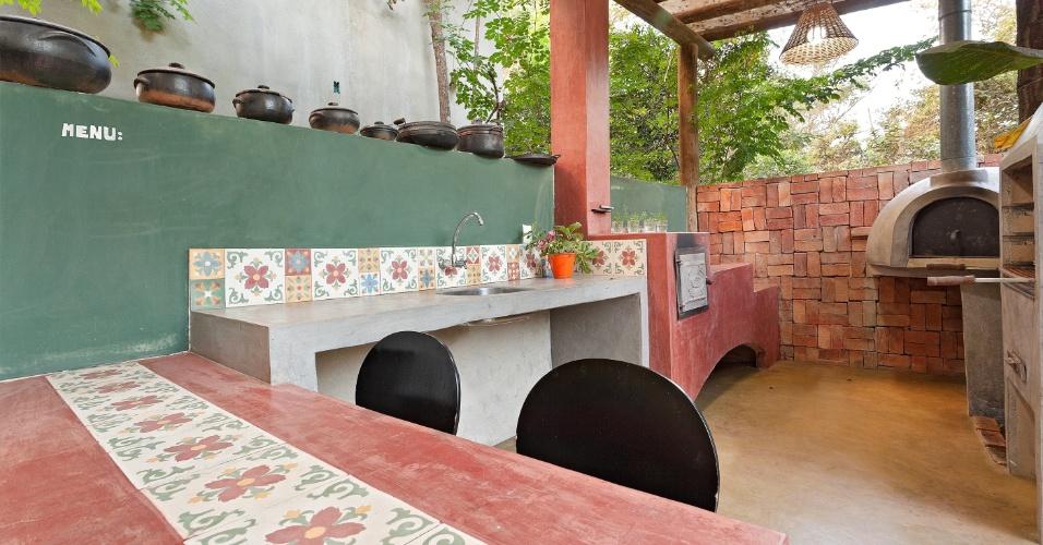 Projetada pela designer de interiores Fabiana Visacro, a cozinha externa possui fogão a lenha feito com tijolo refratário e revestido de cimento queimado. Além da peça, o espaço decorado com ladrilho hidráulico e parede de tijolinho tem forno de pizza e churrasqueira (à dir.)