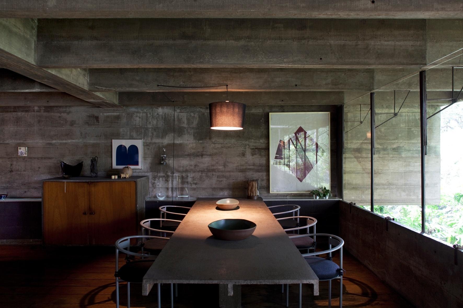 O concreto aparente domina a cena da sala de jantar: o material está tanto na estrutura, quanto na empena cega e até mesmo na mesa de refeições, que foi engastada na parede e está apoiada em apenas um pilar na extremidade oposta. A casa Butantã foi projetada pelo arquiteto Paulo Mendes da Rocha