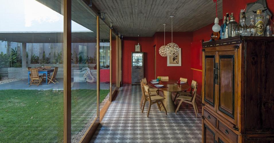A sala de jantar tem teto em concreto aparente, que dialoga com o piso de ladrilho hidráulico e cria contraste harmonioso com as paredes vermelhas. A casa Lapa é um projeto do escritório Brasil Arquitetura