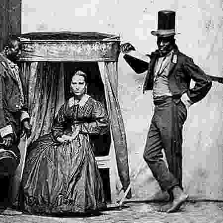 Mulher branca em cadeira que era carregada por dois escravos no Brasil Colônia - Reprodução/Facebook - Reprodução/Facebook