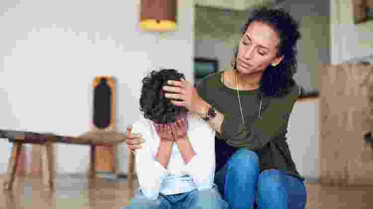Criança chorando ao lado da mãe - laflor/iStock - laflor/iStock