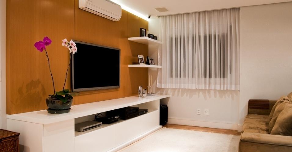 O ambiente com 13 m², idealizado pela arquiteta Paloma Cardoso, se diferencia pelo painel da TV em madeira (freijó), que leva iluminação embutida. O recurso aquece o ambiente e destaca o aparador branco que contém os equipamentos e acopla o