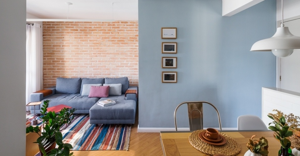 Para dar dinamismo ao living, a arquiteta Marcela Madureira - que assina a reforma do apê Caravelas - diversificou o revestimento das duas paredes: a do fundo recebeu tijolos de demolição e a da entrada ganhou pintura azul. A cor, aliás, é pontuada nas faixas de um dos tapete e a totalidade do outro