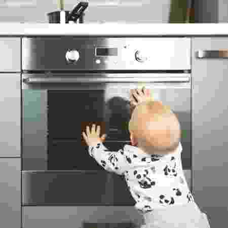 Criança prestes a se queimar no fogão - iStock - iStock