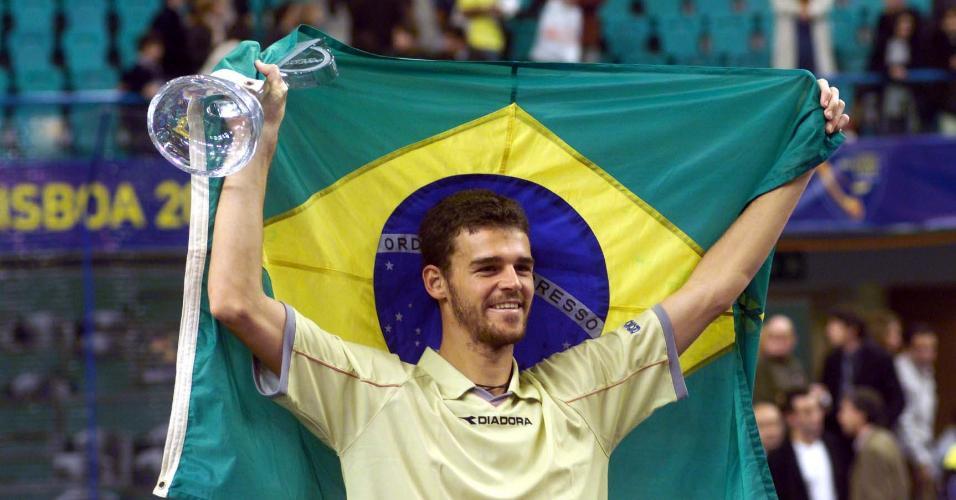 O tenista brasileiro Gustavo Kuerten levanta o troféu e a bandeira brasileira após conquistar o torneio Master Cup ao derrotar o americano Andre Agassi por 3 sets a 0 (6/4 6/4 6/4)no Pavilhão Atlântico do Parque das Nações, em Lisboa, Portuga