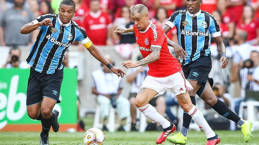 """D""""Alessandro, do Internacional, disputa lance com David Braz e Cortez, do Grêmio - Pedro H. Tesch/AGIF"""