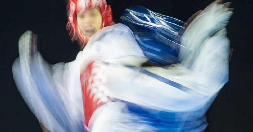 A argentina Celina Proffen (de vermelho) acerta a panamenha Carolina Carstens na disputa do taekwondo até  57kg