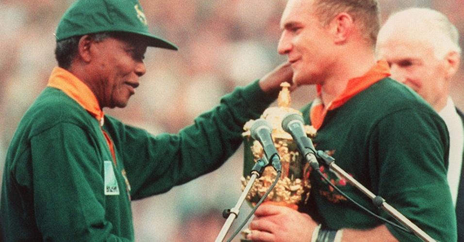 François Pienaar, capitão da seleção sul-africana de rúgbi, recebe o troféu da Copa do Mundo da modalidade em 1995 das mãos do presidente da África do Sul, Nelson Mandela