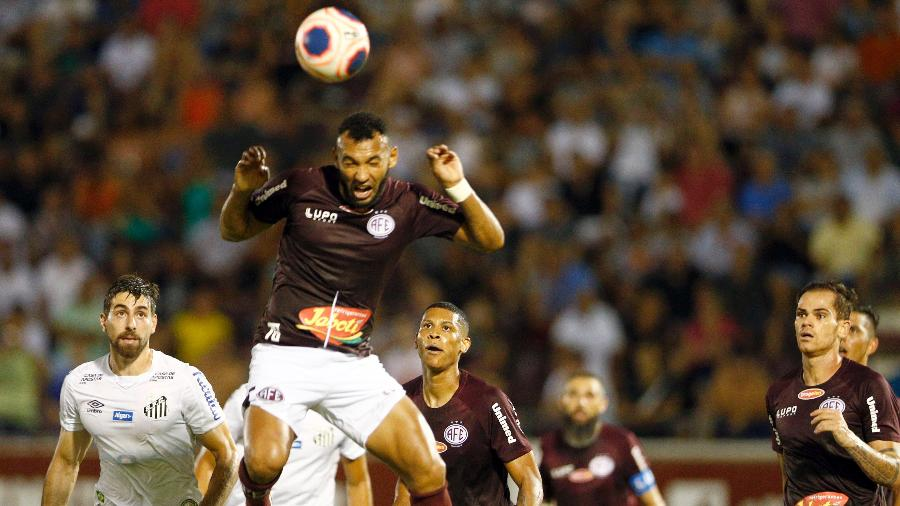 Jogador da Ferroviária afasta de cabeça, durante o jogo com o Santos - Thiago Calil/Thiago Calil/AGIF