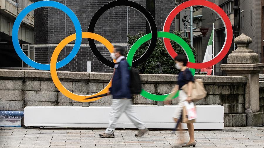 Pessoas usando máscaras contra covid-19 passam em frente aos anéis olímpicos em Tóquio, no Japão - Takashi Aoyama/Getty Images