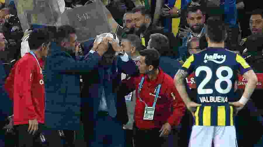 Senol Gunes, técnico do Besiktas, coloca a mão na cabeça após ser atingido por objeto - AFP PHOTO / STRINGER