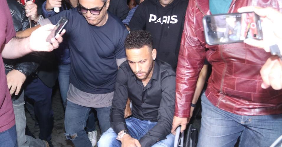 Neymar chega à delegacia no Rio e é empurrado em cadeira de rodas