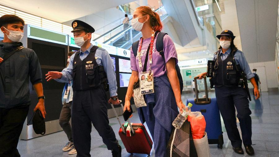 Krystsina Tsimanouskaya é acompanhada por policiais no aeroporto de Tóquio; ela chegou a ser forçada para retornar à Belarus - Issei Kato/Reuters
