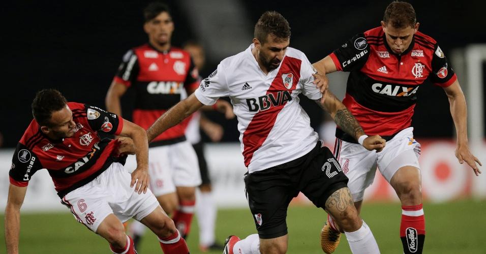 Lucas Pratto encara marcação dupla de Renê e Jonas no jogo entre Flamengo e River Plate, pela Libertadores