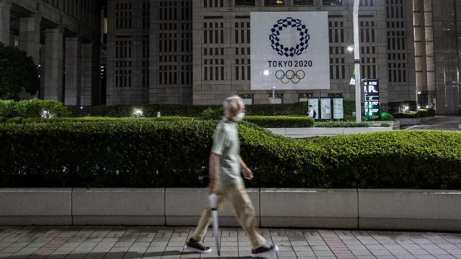 De máscara contra o coronavírus, homem anda em frente a um dos banners dos Jogos Olímpicos de Tóquio - TTakashi Aoyama/Getty Images