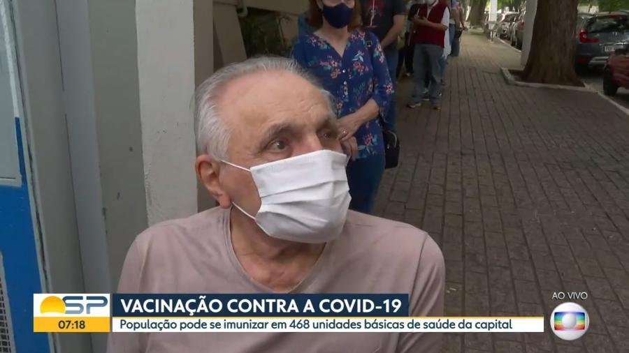 O ex-narrador do grupo Bandeirantes Alexandre Santos deu entrevista para a TV enquanto aguardava vacina - Reprodução