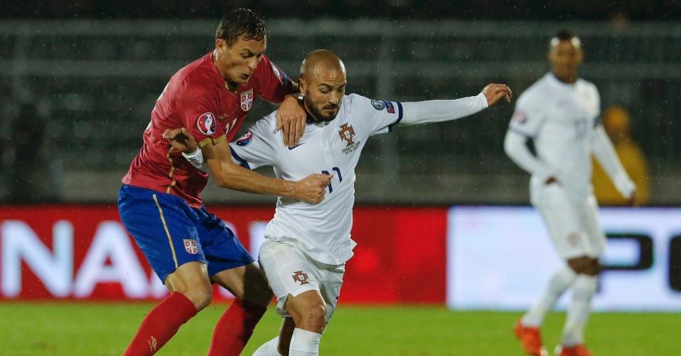 Matic, da Sérvia, tenta tomar a bola de André, de Portugal, em jogo válido pelas Eliminatórias para a Euro 2016